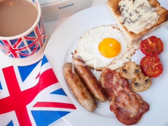 Bacon and eggs with cup of tea, toast and british flag